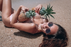 Healthy lifestyle. Girl holding juicy pineapple and relaxing on sunny evening coast . Stylish summer outfit. Holiday mood. Beach party.